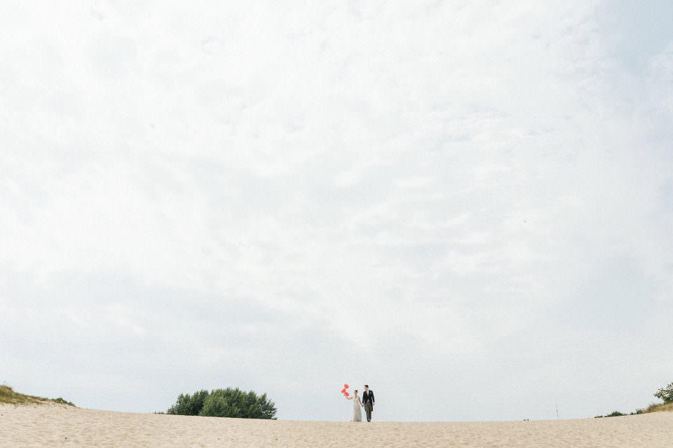 Ein Brautpaar mit einem Luftballon steht in einer Landschaft