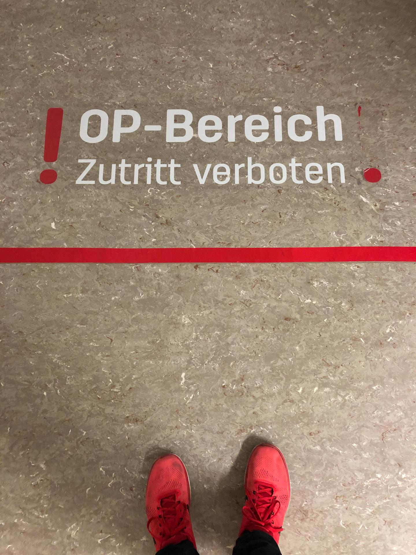Zwei Schuhe auf dem Boden vor einem OP-Bereich