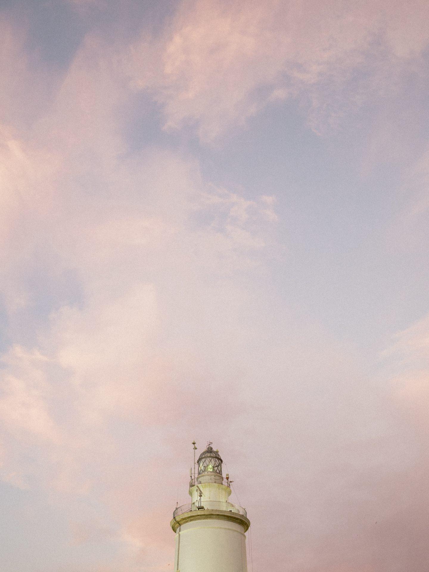 Ein Leuchtturm vor einem bewölkten Himmel bei Sonnenuntergang